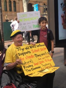 Late Sutherland based environmental activist, Bill Ryan, protests for climate action with young boy