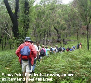 """An image of a column of bushwalkers traversing a landscape of trees and ferns. Image is captioned with """"Sandy Point Residents crossing former military land near Mill Creek"""""""