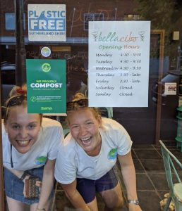 An image of two women in the window of Bella Cibo cafe with sustainable practices certificates